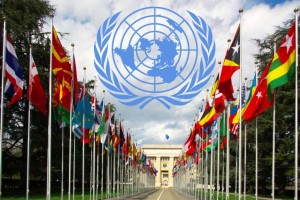Photo of the national flags gallery at the entrance to UN with the UN logo superimposed above it