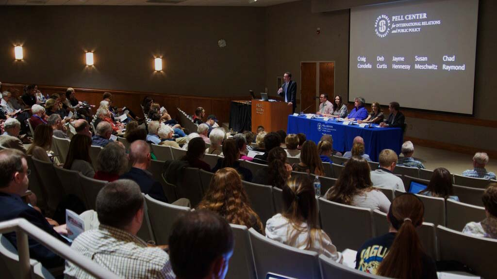 Pell Center Executive Director Jim Ludes moderates the lecture about Pope Francis' encyclical letter as panelists Craig Condella, Deb Curtis, Jayme Hennessy, Susan Meschwitz and Chad Raymond look out upon a crowd of Salve students and Newport community members