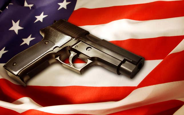 Photograph of a handgun resting on top of an American flag.
