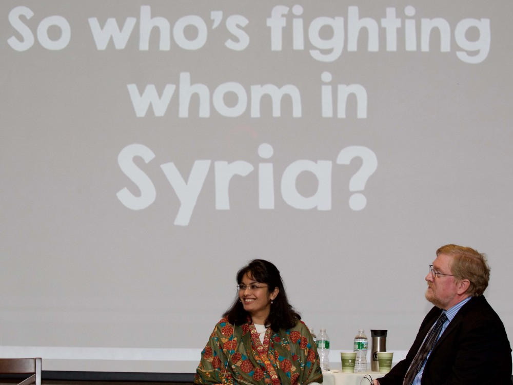 Hayat Alvi and Timothy Hoyt speak onstage during their lecture about United States policy in the Middle East.