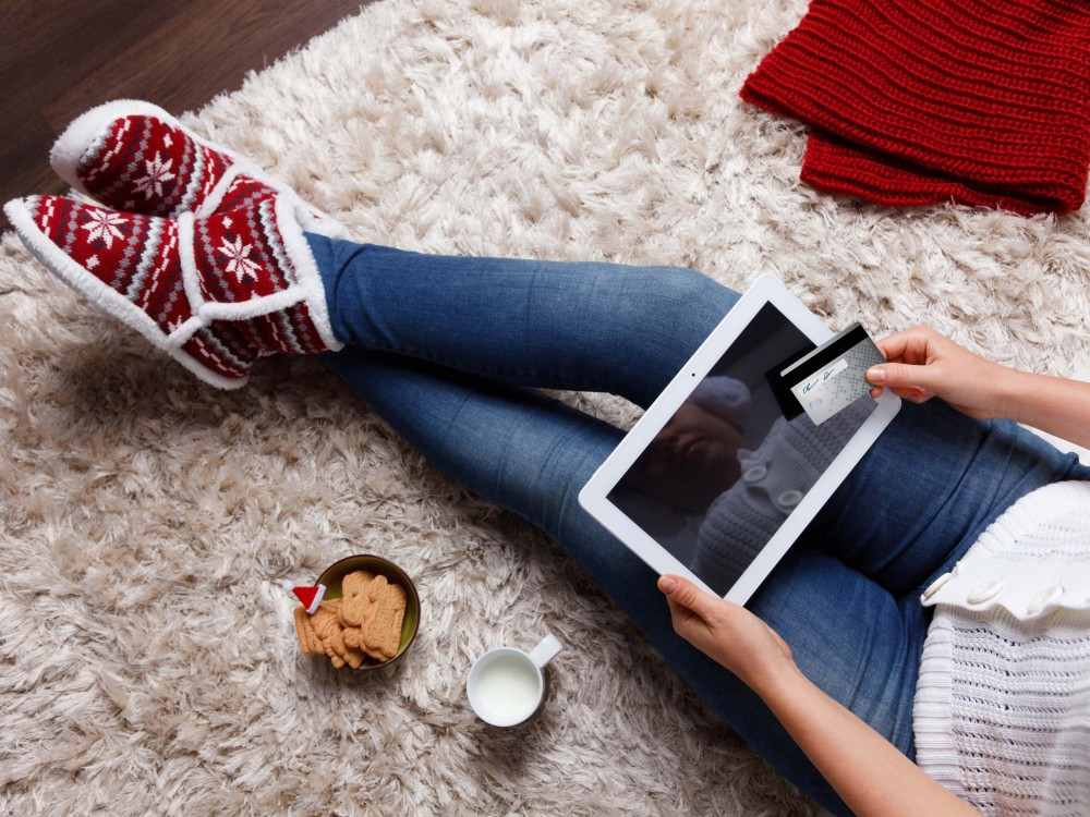Woman holding a digital tablet and a credit card in seasonal attire on a shag rug with milk and Christmas cookies.