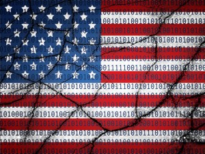 Image of the American Flag covered in ones and zeroes and cracked in pieces to represent a cracked cyber code.