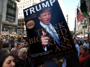 Photo of a person holding a life-size version of the cover of Donald Trump's book, Think Big and Kick Ass In Business and Life, among a crowd of others.