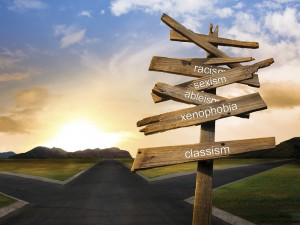 A visual representation of the term intersectionality with a wooden sign placed at a crossroads pointing the way towards racism, sexism, ableism, xenophobia and classism.