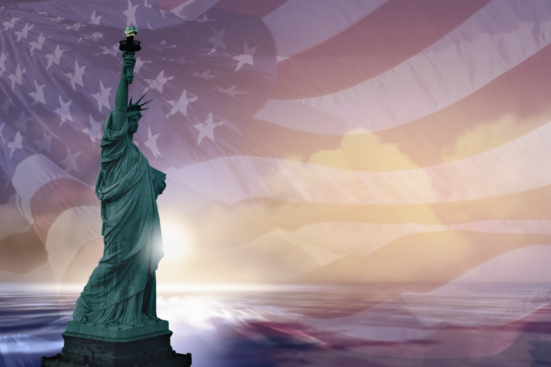 Image of the Statue of Liberty at sunset superimposed over a waving American flag.