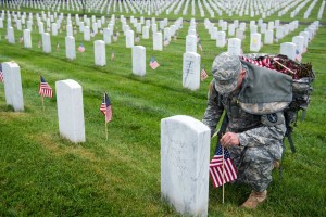 Soldier placing American flag at the base of each stone in Arlington National Cemetery.