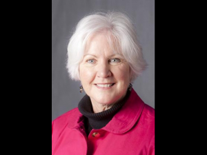 Head shot of Dr. Martha McCann Rose wearing a pink jacket and smiling at the camera.
