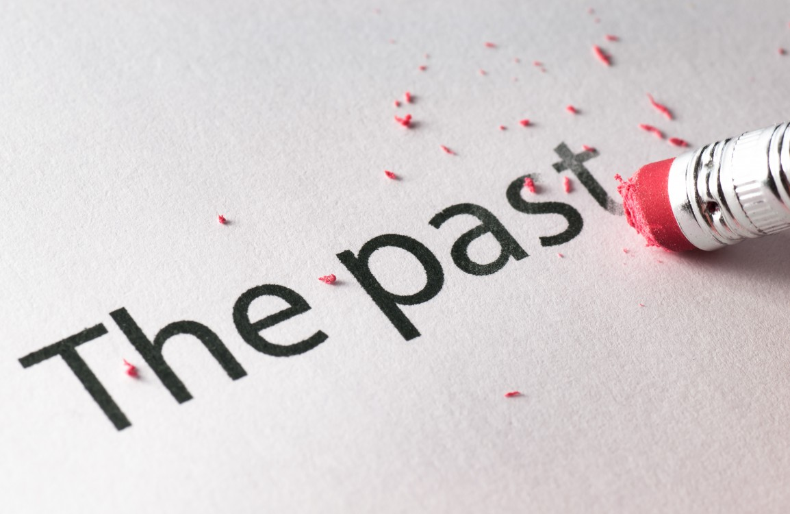 "Pencil erasing the words ""the past"" from a white page."