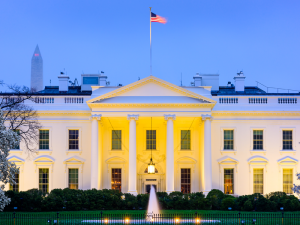 Image of the front of the White House at nighttime with an American flag flying proudly upon the rooftop.