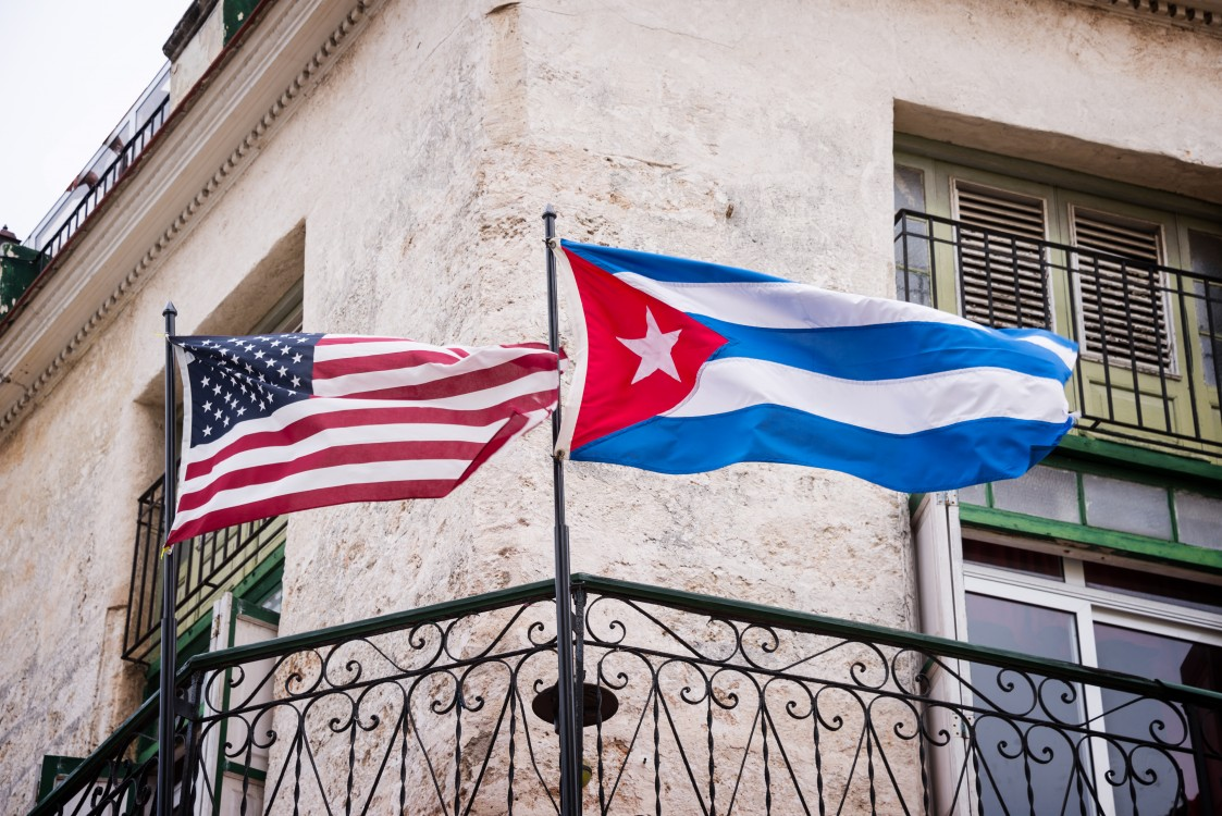 The American and Cuban flags fly side by side on a balcony in Havana, Cuba.