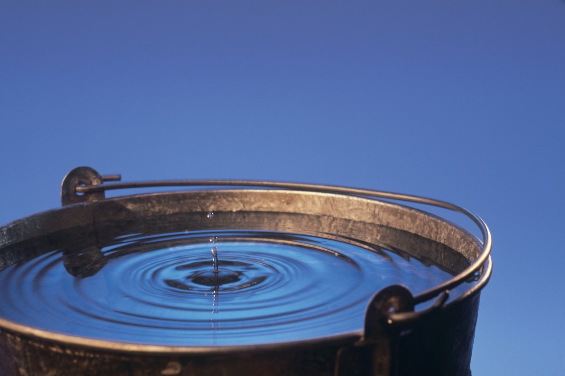 Close-up photo of a water droplet impacting the surface of a water bucket.