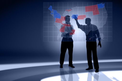 Two men ponder which states will end up Republican and Democratic in front of a map of the United States.