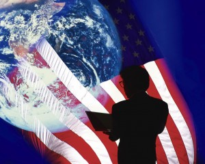 Image of a Businessman Holding a Laptop, Surrounded By an American Flag and the Planet Earth