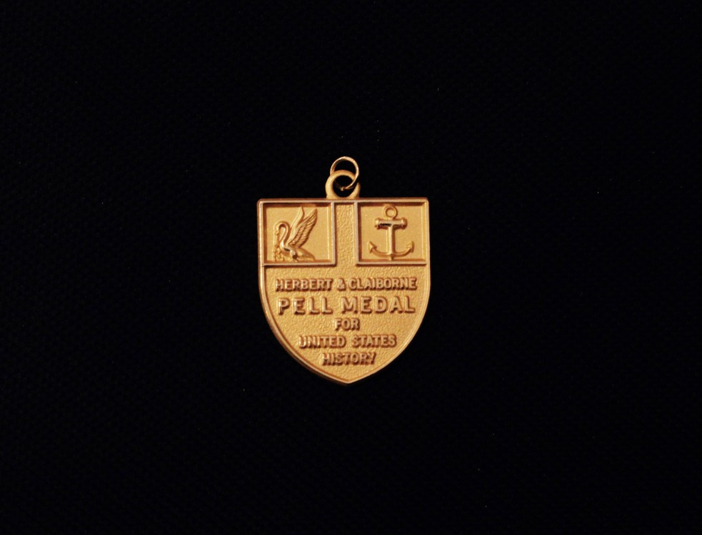 Image of the Herbert and Claiborne Pell medal for United States History on a black background.