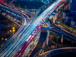 Long exposure photo of cars on a highway overpass. The left lane is a blur of white showing the traffic moving while the right lane is a dotted canvas of tail lights showing a major traffic jam. Soft blues from a twilight sky mix with the rough orange of urban life. Streetlights in the background reveal a world underneath the overpass one that is dark both metaphorically and literally. The photo shows concrete life coming to fruition. The buildings, the overpass itself, all of the same material. What is this urban life? It is a complex mix of blue and orange on a concrete palette drowning out the cries of a lonely green park. Just a hint of the once expansive natural wonder of this land exists surrounded by the overpass, another metaphor. The overpass is layered much like the way we experience life. While we may wait trapped in traffic above, below the cars race to and fro, trapped in an inevitable push for space. Amidst the chaos of urban life a red light frees lanes in the bottom right. Show the constructed nature of this problem we call traffic. By mans design traffic comes and goes, ebbing and flowing not from the tides but from the red lights that dot the image.