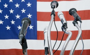 A series of microphones sitting in front of an American flag