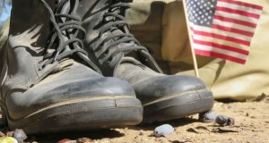 Combat boots on the ground next to a small American Flag